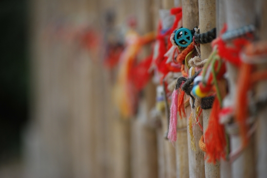 At the killing fields of Cambodia, many of the tourists leave their bracelet on the bamboo fences that mark the edges of burial sites, as a token of compassion.