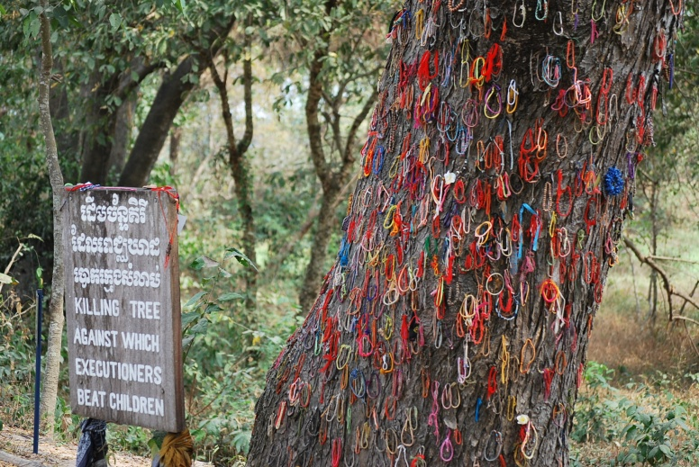 Bracelets are left on the tree by tourists in sympathy with the child victims that were beaten to death at this tree only several decades ago.