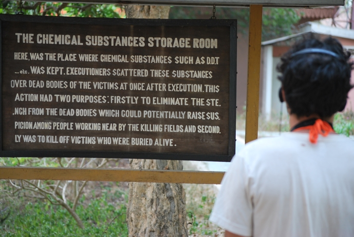 The sign this tourist is looking at reads that toxins were poured over the bodies not only to cover up the smell of the rotting corpses, but at the same time ensuring that any surviving victims playing dead would surely die...